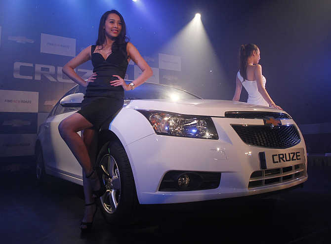 Models pose next to Chevrolet Cruze in Hanoi, Vietnam.