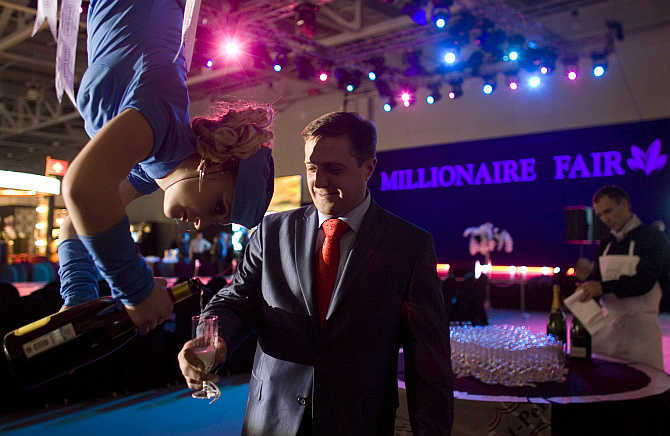 A woman, suspended from the ceiling, serves champagne to a man at the Millionaire Fair in Moscow.