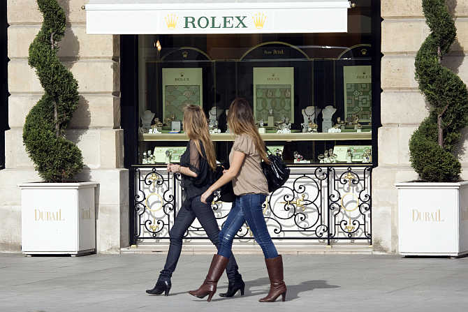 Women walk past a window display of luxury goods maker Rolex in Paris's Place Vendome.
