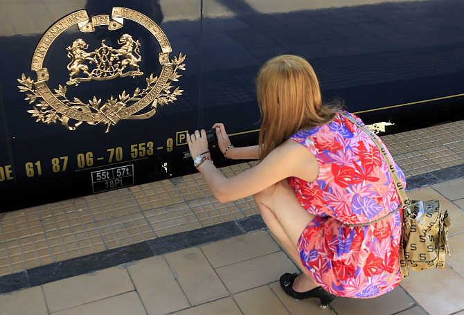 A woman takes a picture of the logo of the Orient Express luxury train at the main railway station in Bucharest, Romania.