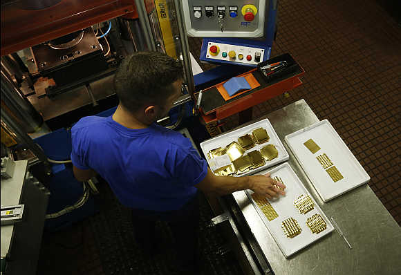 An employee places a gold Combibar into a press machine in Balerna, Switzerland.