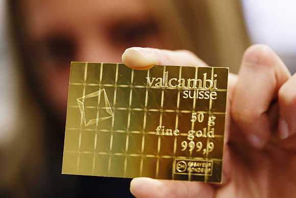An employee shows a gold Combibar in Balerna, Switzerland.