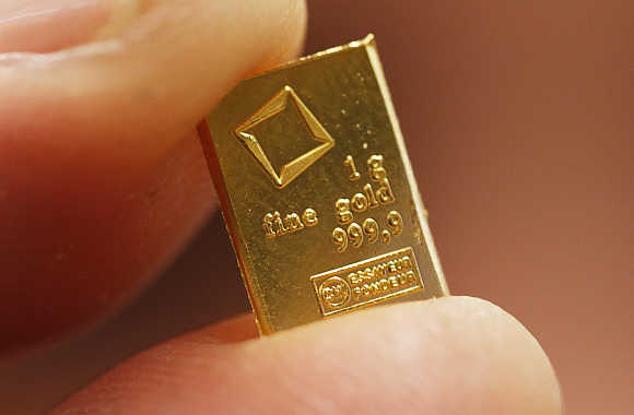 An employee shows a one gram piece of a gold Combibar in Balerna, Switzerland.