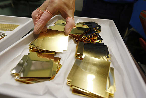 An employee holds an unpressed gold Combibar in Balerna, Switzerland.