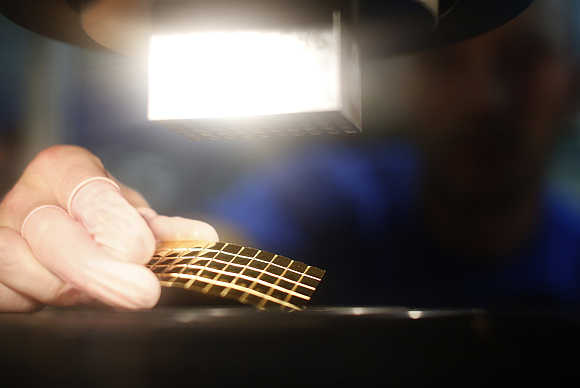 An employee places a gold Combibar in Balerna, Switzerland.