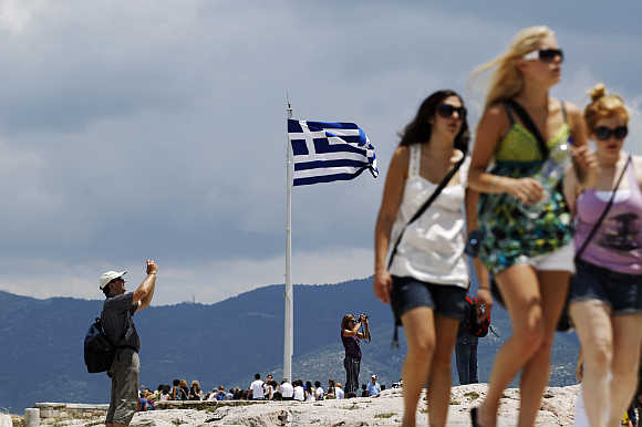 Tourists visit the archaeological site of the Acropolis hill in Athens.