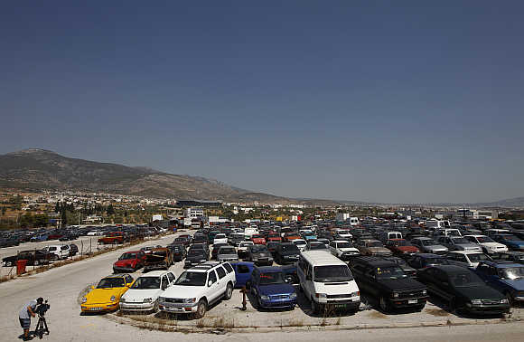 A cameraman films confiscated cars in a yard of Oddy in Athens.