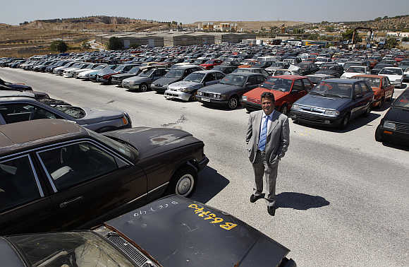 Oddy's Manager Dimitris Kouvaris amid confiscated cars in the yard in Athens.
