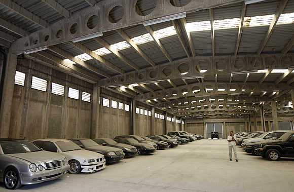 A man walks by confiscated luxury cars inside a warehouse of Oddy in Athens.