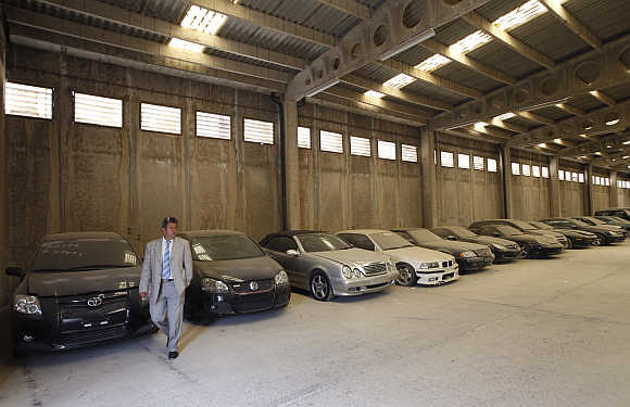 Oddy's Manager Dimitris Kouvaris walks by confiscated luxury cars in the warehouse in Athens.