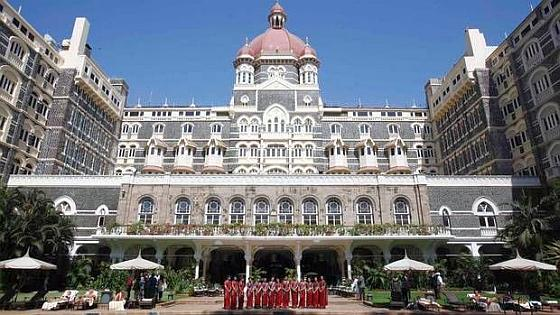 Staff of the Taj Mahal Palace hotel pose in Mumbai.