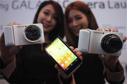 Models pose with sets of Samsung Electronics' Galaxy Camera during its launch event.