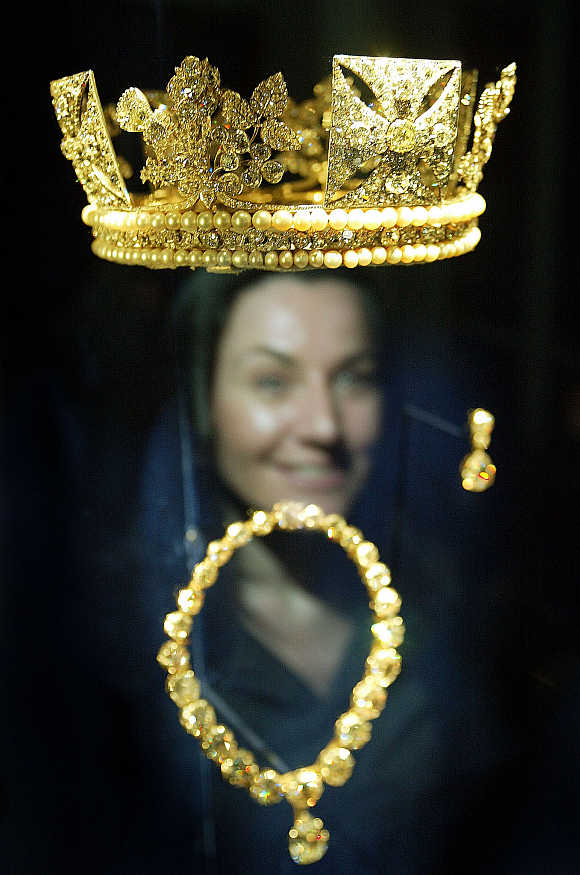 A woman looks at the Diamond Diadem Crown (1820), which belongs to Britian's Queen Elizabeth II, at the Queen's Gallery at Buckingham Palace in London.
