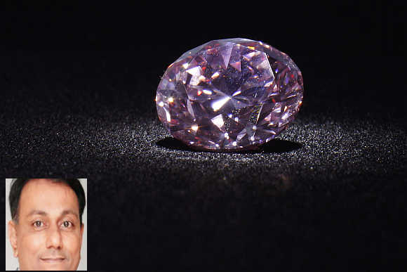 'Martian Pink', a 12.04-carat Fancy Intense pink (Type IIa) diamond, is shown during a media preview at Christie's in Hong Kong. Dharmesh Shah, inset.
