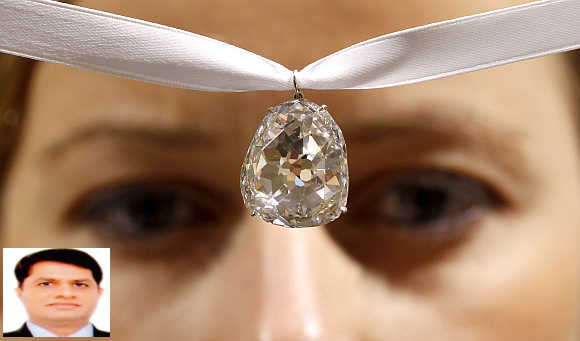 An employee of Sotheby's auctioneers displays the Beau Sancy diamond in Zurich, Switzerland. Ashok Gajera, inset.