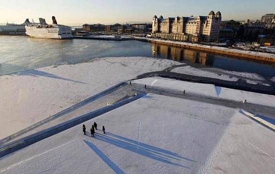 Pedestrians walk by the harbour during winter in Oslo.