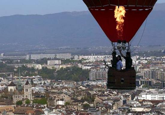 balloonist uses his burner during a flight above the city of Geneva.