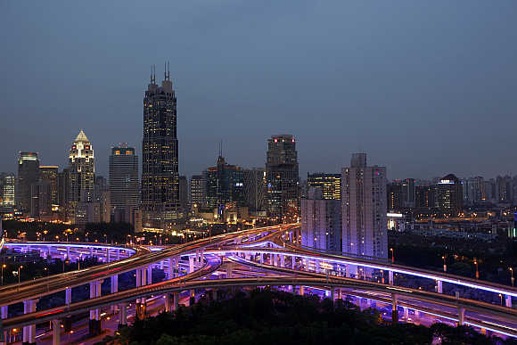 An aerial view shows vehicles travelling on intersections at night in downtown Shanghai.