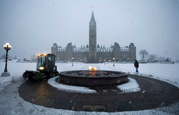 A worker cleans away snow around the Centennial Flame on Parliament Hill in Ottawa.