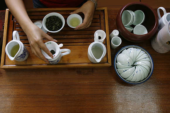 A woman prepares 'Bao Zhong' tea using a traditional tea set in Pinglin. The small town is one of Taiwan's major tea growing areas and is located in the mountains which provides an ideal climate for growing tea.