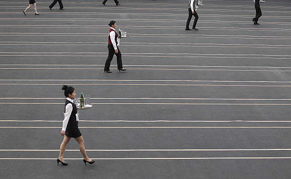 Contestants race with trays containing beer bottles and glasses during the Wowprime tray carrying competition in Taipei, Taiwan. Over 1,200 waiters and waitresses from around Taiwan compete in the race based on speed, grace, and accuracy for prizes worth about $8,200 and working opportunities at restaurant chain operator Wowprime Corp.