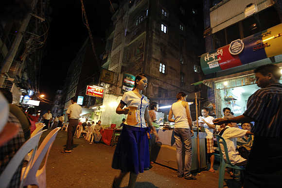 A girl carries a beer jar in Yangon's beer street in Myanmar.