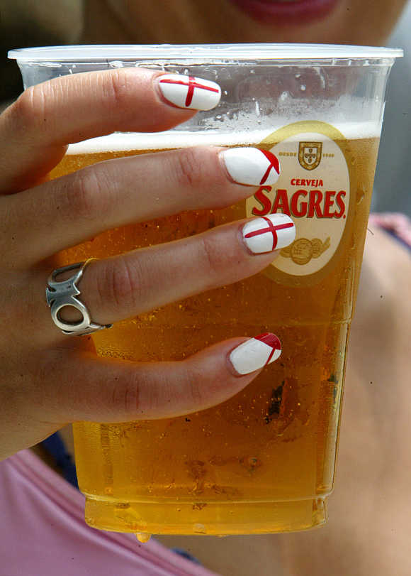 A England fan holds a glass of beer in the centre of Lisbon, Piortugal.