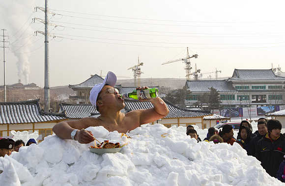 Jin Songhao drinks beer as he sits in snow during a cold endurance performance in Yanji, Jilin province. Jin set the Guinness record for the longest time spent in direct full body contact with snow with a time of 46 minutes and seven seconds.