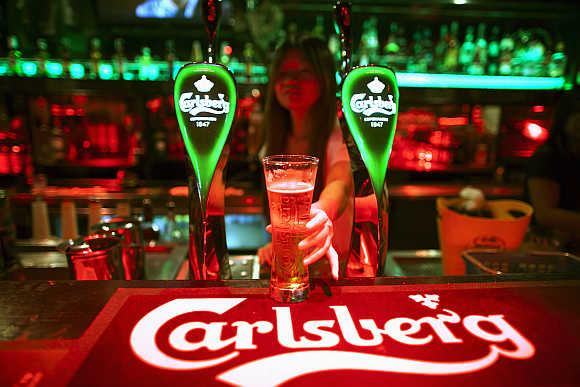 A bartender serves a beer at a bar in Kuala Lumpur, Malaysia.