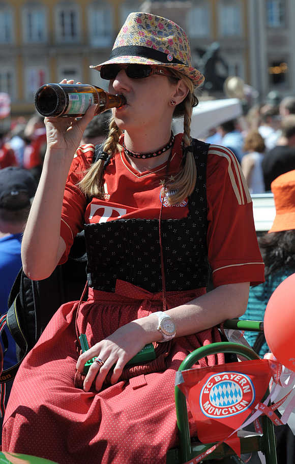 A Bayern Munich supporter drinks beer in downtown Munich Germany.