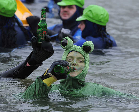 A swimmer wearing a costume drinks beer while swimming in the near-freezing water of the river Danube in Neuburg an der Donau, Germany.