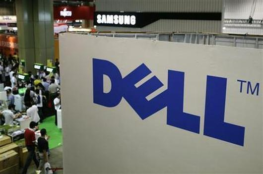 Shoppers walk past a Dell booth.
