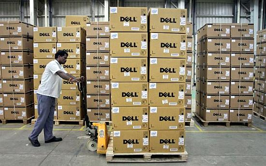 A man pushes a trolley full of Dell computers through a company factory.