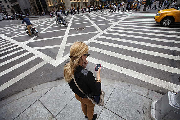 A woman uses her Apple iPhone while waiting to cross 5th Avenue in New York.