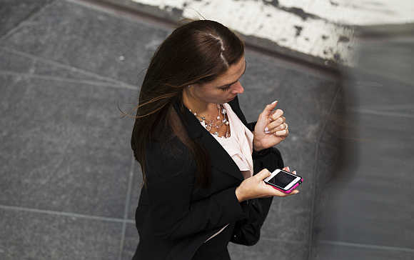 A woman uses her Apple iPhone while walking through Times Square in New York.