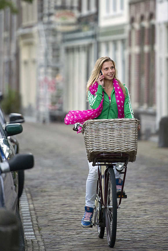A woman cycles while talking on a phone in Alkmaar, the Netherlands.