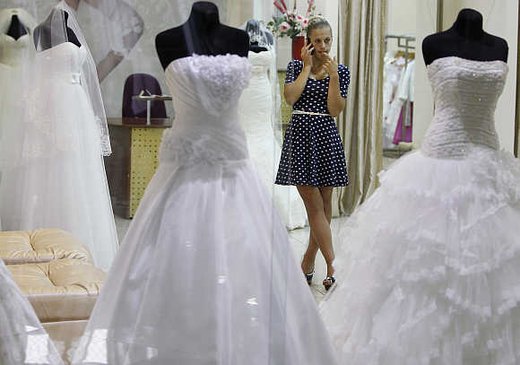 A shop assistant talks on the phone at a bridal gown store in a shopping mall in Kiev, Ukraine.