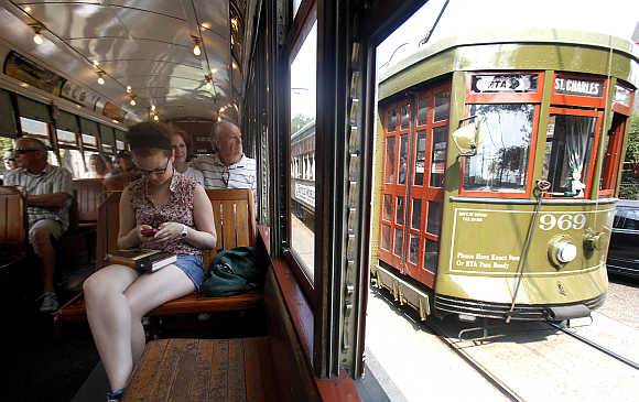A woman works on her smartphone as she travels down the St Charles Avenue Street Car line in New Orleans, United States.