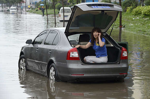 A woman talks on her mobile phone inside the trunk of her car as she waits for rescue on a flooded street in Taiyuan, Shanxi province, China.