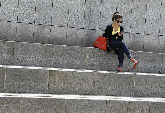 A woman uses her mobile phone as she rests in Independence Square in central Kiev, Ukraine.