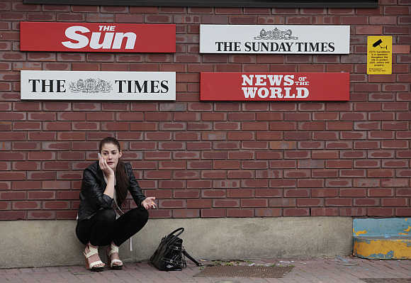 A woman speaks on her mobile phone outside the News International HQ building, in east London.