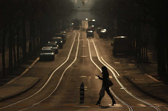 A woman crosses a street while using a mobile phone in Bern, Switzerland.