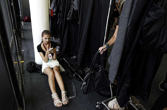 A model uses her mobile phone backstage before Osklen's Winter collection during Sao Paulo Fashion Week.