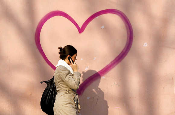 A woman talking on her mobile phone walks past a heart-shaped graffiti in Bucharest, Romania.