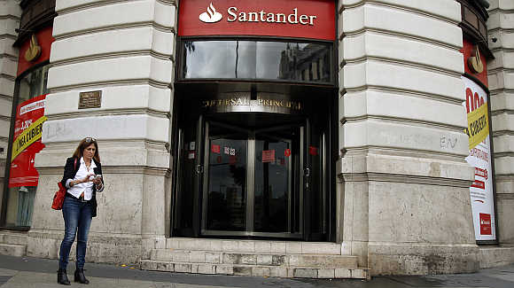 A woman uses her mobile phone outside the main branch of Spain's Santander bank in Madrid.