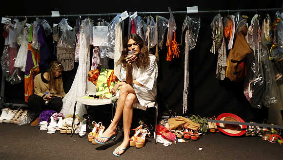 A model checks her phone backstage before the Beachwear Spring/Summer 2013 collection at Milan Fashion Week in Italy.