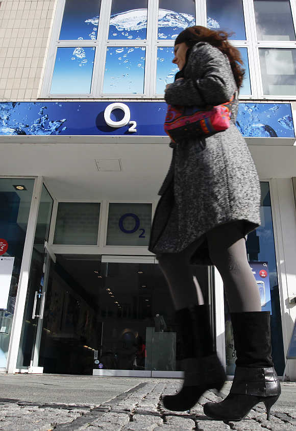 A woman passes by a German mobile phone group O2 shop at Wilmersdorfer shopping street in Berlin.