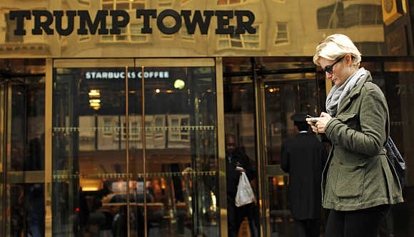 A woman uses her mobile phone in front of the Trump Tower in New York.