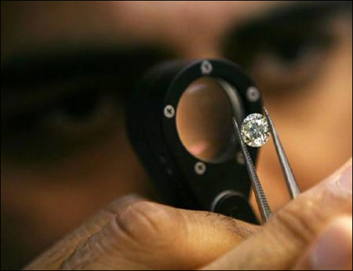 A diamond merchant desmonstrates a process at a diamond cutting and polishing factory in Surat, Gujarat.