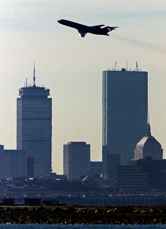 A plane passes Boston's Prudential, left, and John Hancock, right, towers as it takes off from Logan International Airport.